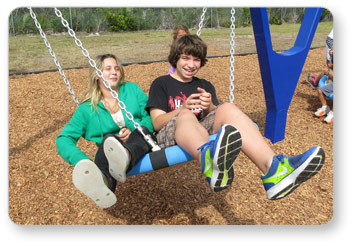 Girl and Boy Swinging on a Biggo Classic Swing
