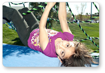 Girl Hanging Upside Down from a Ropes Course